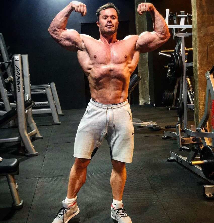 Renato Cariani flexing his arms while being shirtless in the gym