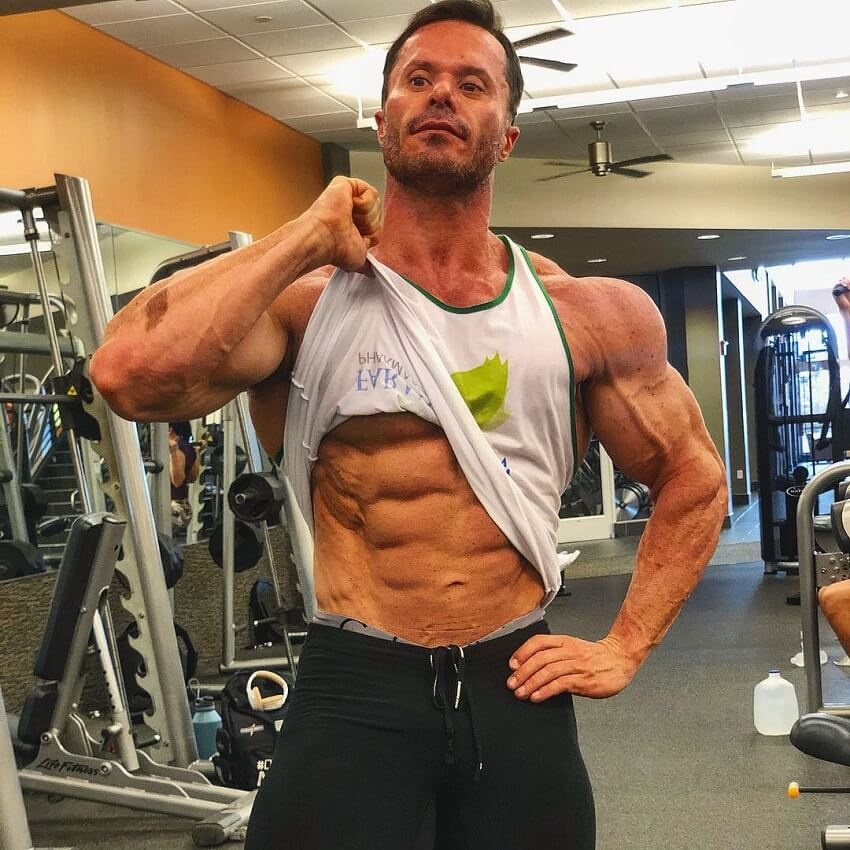Renato Cariani flexing his abs in a gym