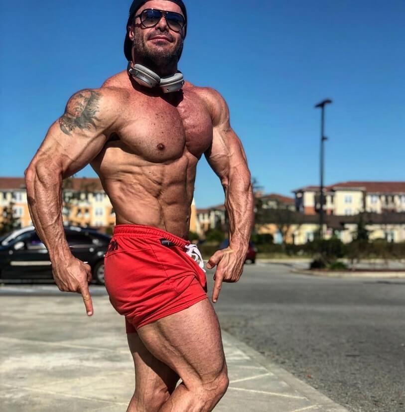 Renato Cariani flexing shirtless outdoors in the sun