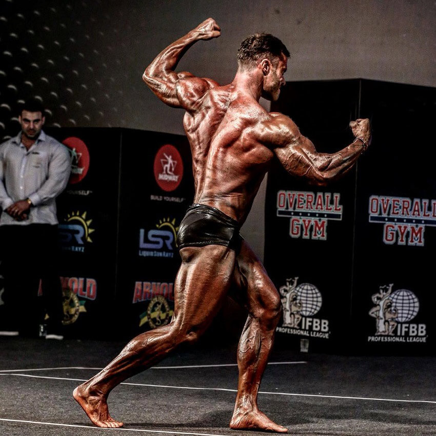 Renato Cariani flexing his back on a bodybuilding stage