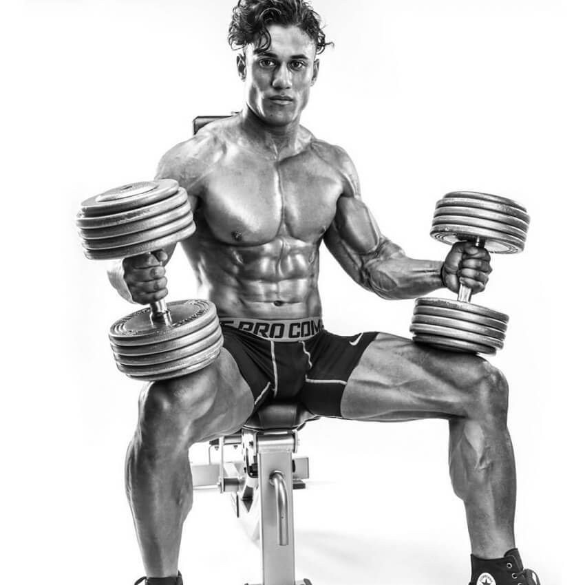 Stephen Pinto sitting shirtless on a bench with dumbbells in his hands