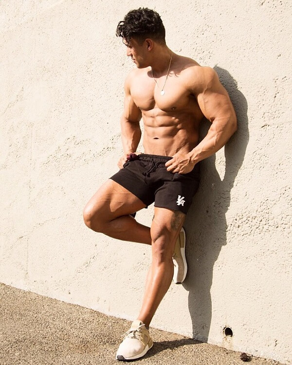 Stephen Pinto leaning against the wall outdoors, shirtless, soaking up the sun