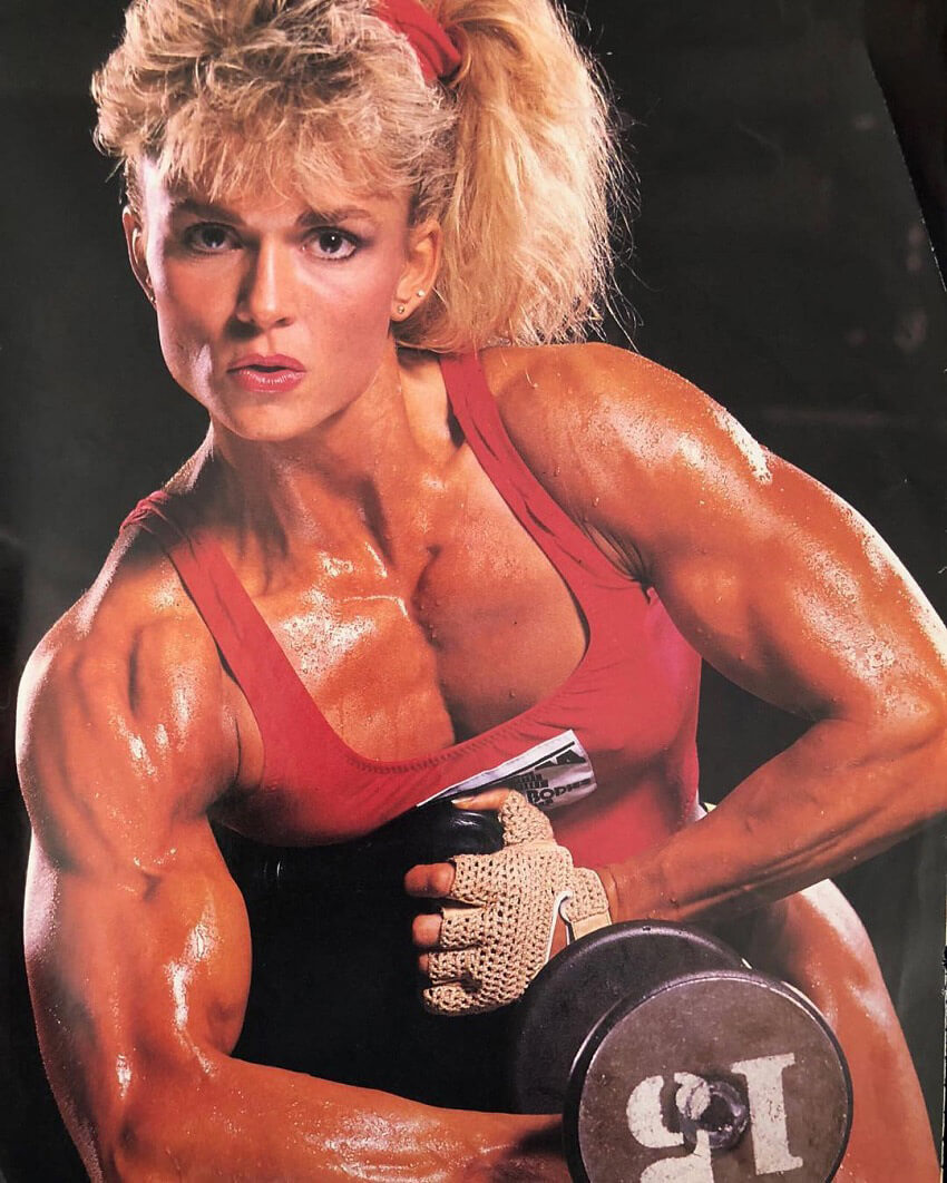 Tonya Knight posing with a dumbbell looking ripped and aesthetic