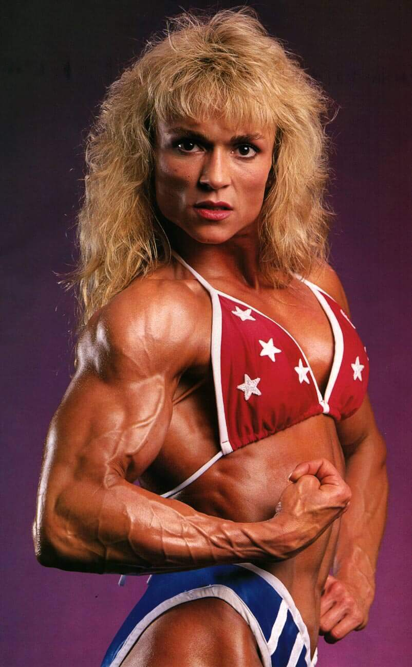 Tonya Knight flexing her biceps from the side, looking vascular and ripped