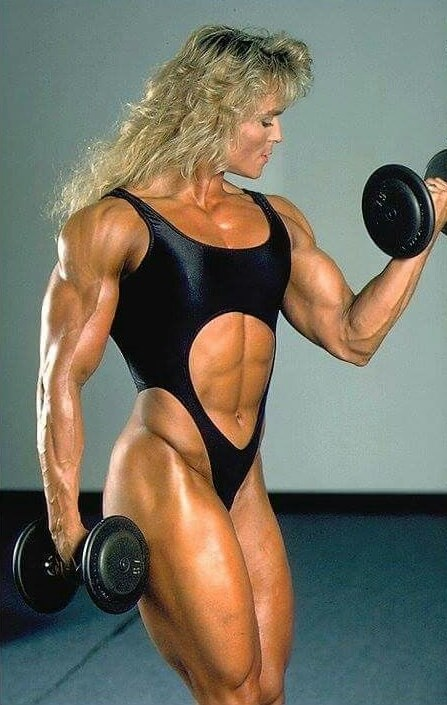 Tonya Knight performing biceps curls, looking ripped and aesthetic