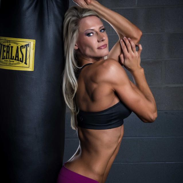 Whitney Jones leaning against a black boxing bag during a fitness photo shoot
