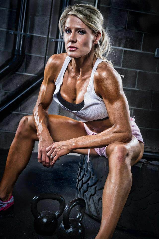 Whitney Jones sitting on a tire looking ripped and fit