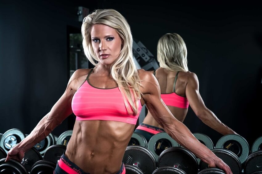 Whitney Jones leaning against dumbbells in the gym, looking fit and lean