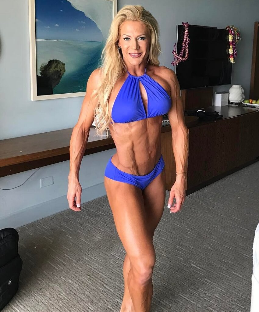 Whitney Jones posing in her room in a bikini, looking extremely ripped and conditioned