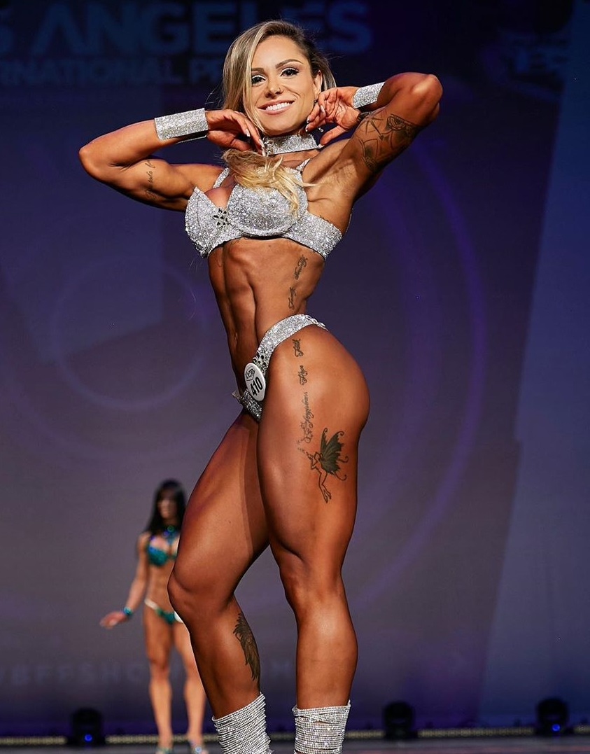 Carol Franca posing on the WBFF fitness stage, looking aesthetic and lean