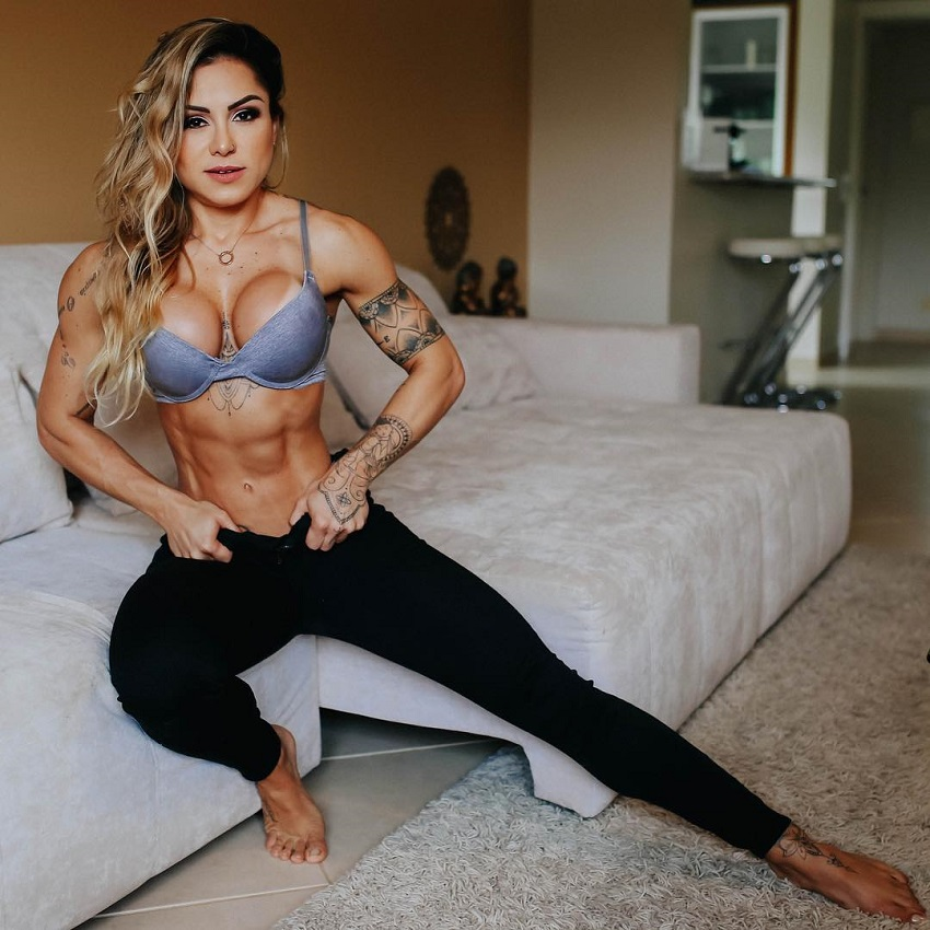 Carol Franca flexing her muscles in her room, looking fit and ripped