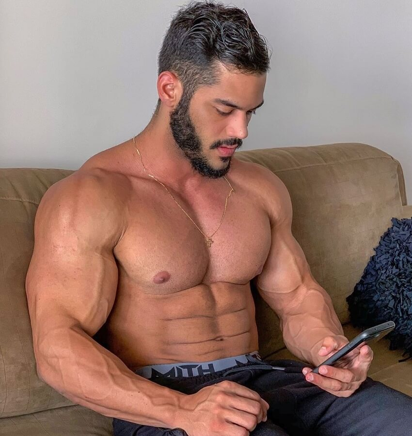 Geder Rocha sitting shirtless on a couch, texting on his phone, looking ripped and muscular