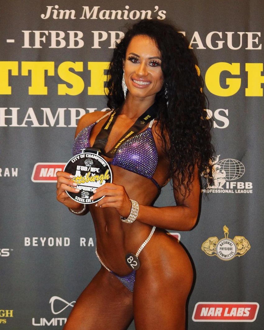 Jennifer Dorie posing backstage with a medal
