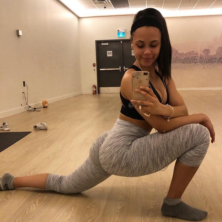 Kali Natesa taking a selfie in yoga room while wearing grey leggings