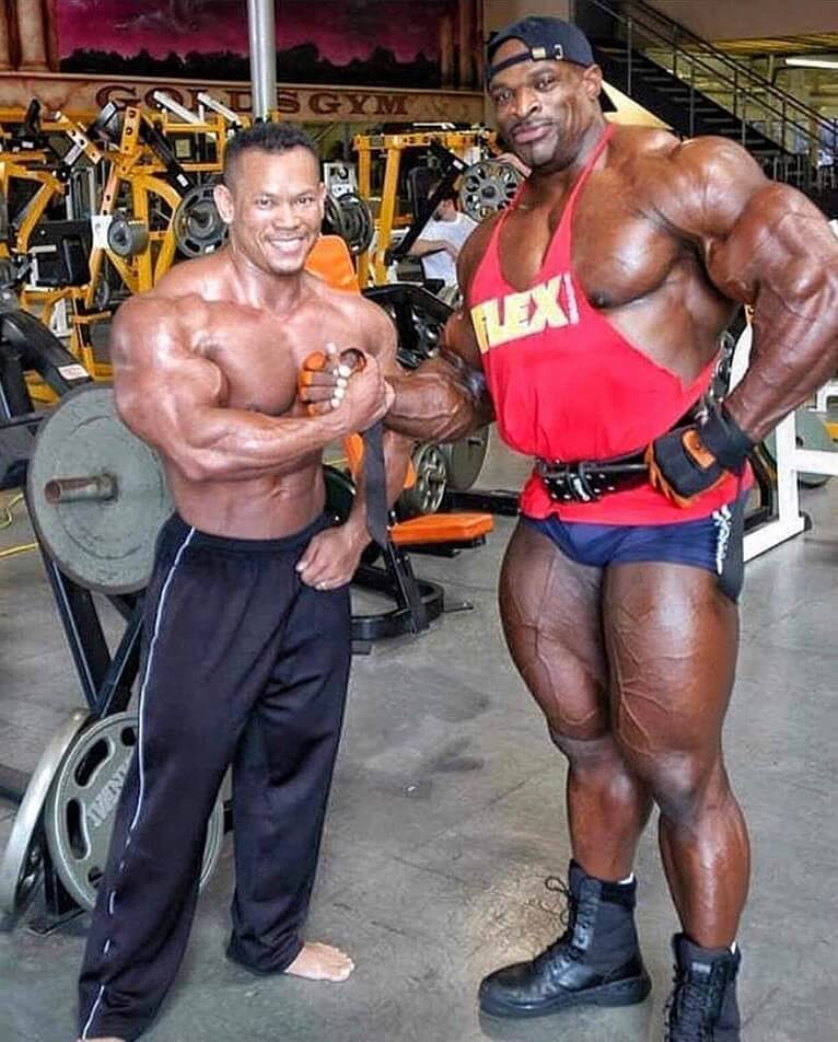 Kris Dim posing in the gym with Ronnie Coleman