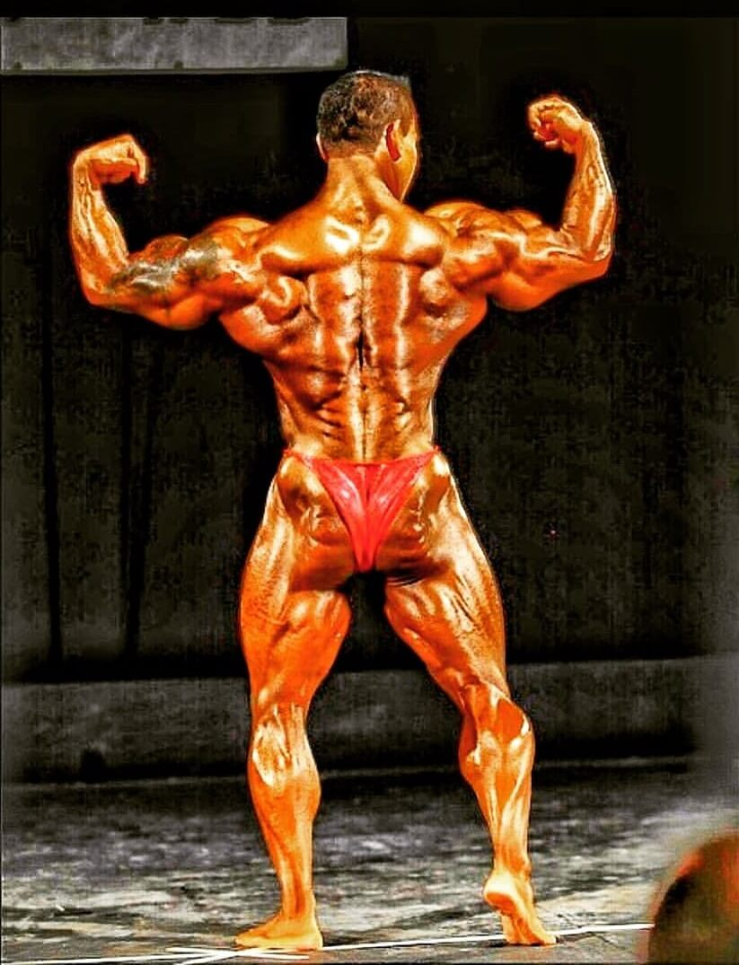 Kris Dim hitting a back double biceps pose on the bodybuilding stage