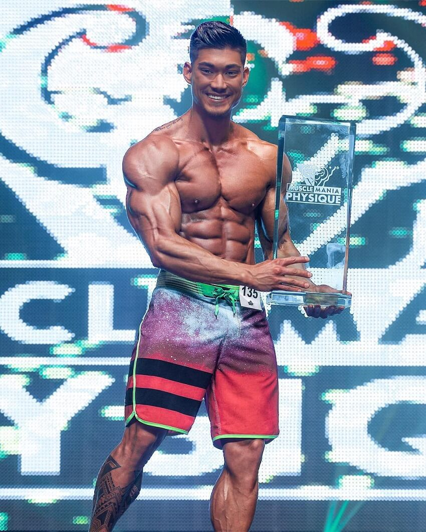 Nicolas Iong posing with a trophy on a bodybuilding stage