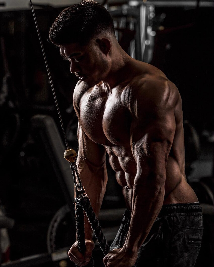 Nicolas Iong doing shirtless triceps extensions