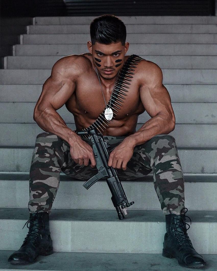 Nicolas Iong sitting shirtless wearing military pants and holding a gun