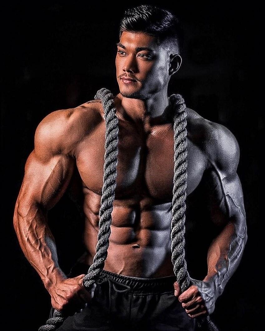 Nicolas Iong posing shirtless with training ropes around his neck