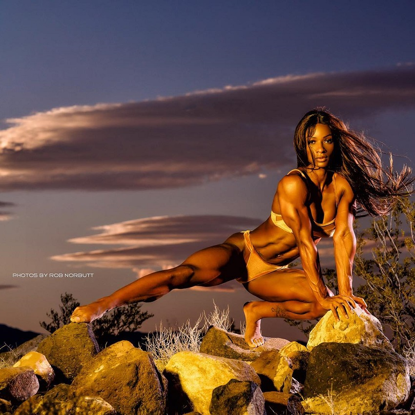 Candice Carter posing on a rock in a bikini looking fit and lean