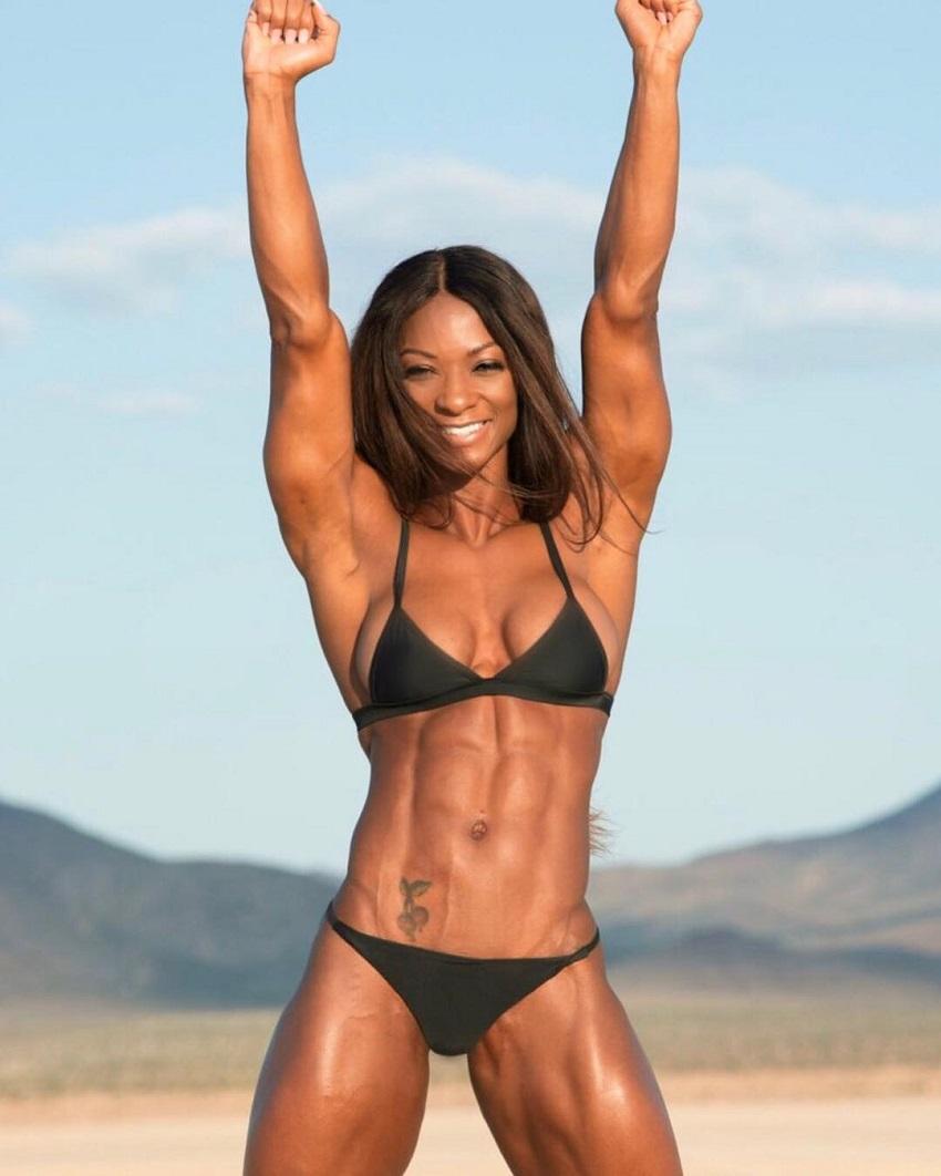 Candice Carter posing happily in a black bikini outdoors