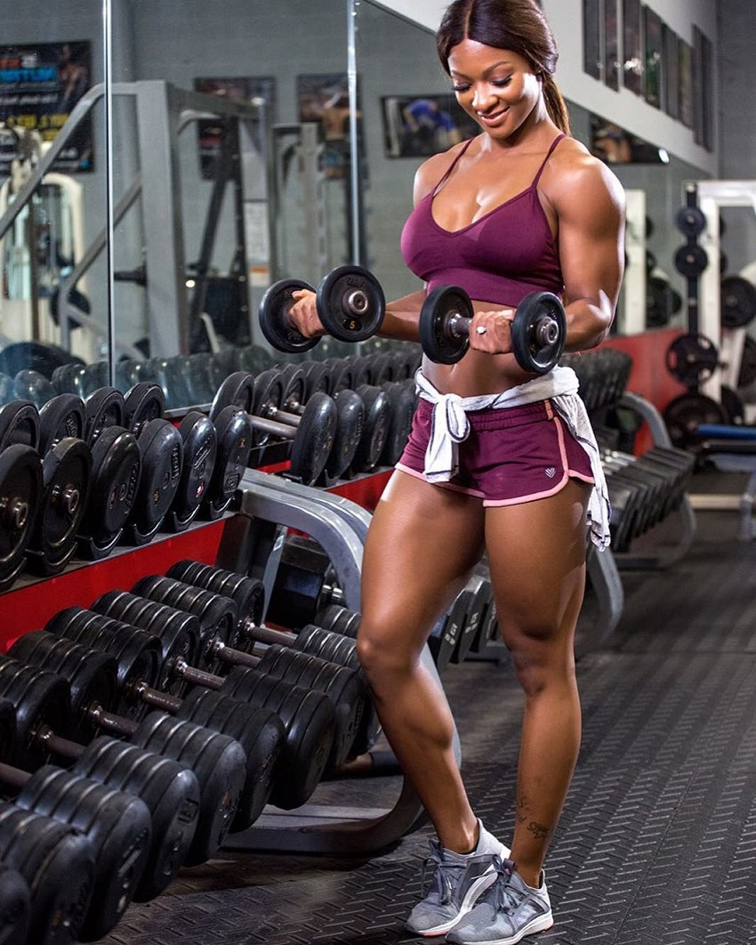 Candice Carter doing biceps curls in the gym