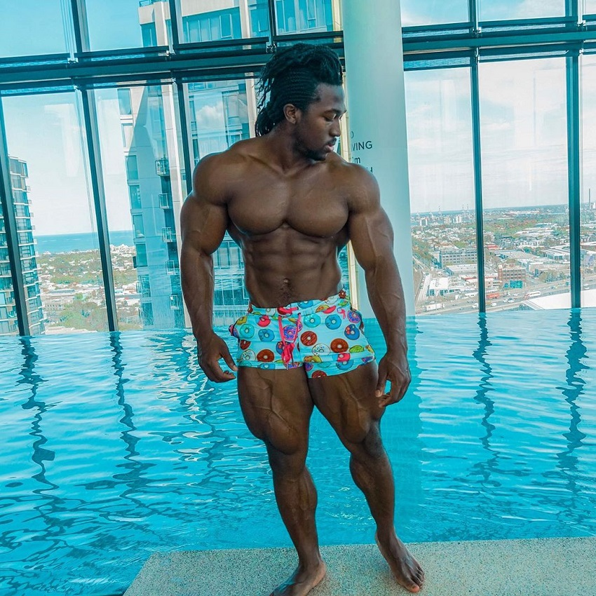 Kwame Duah posing shirtless by the pool looking swole and aesthetic