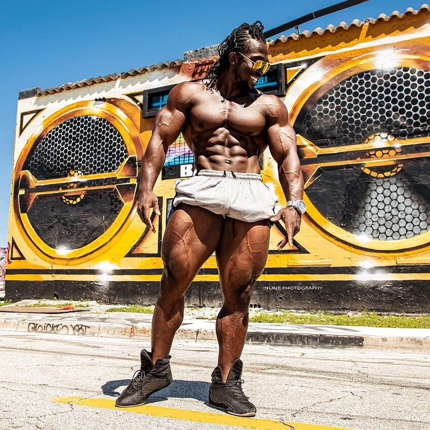 Kwame Duah posing shirtless outdoors, looking huge and ripped