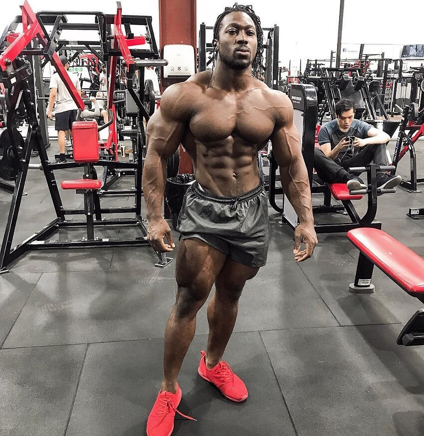 Kwame Duah posing shirtless in the gym