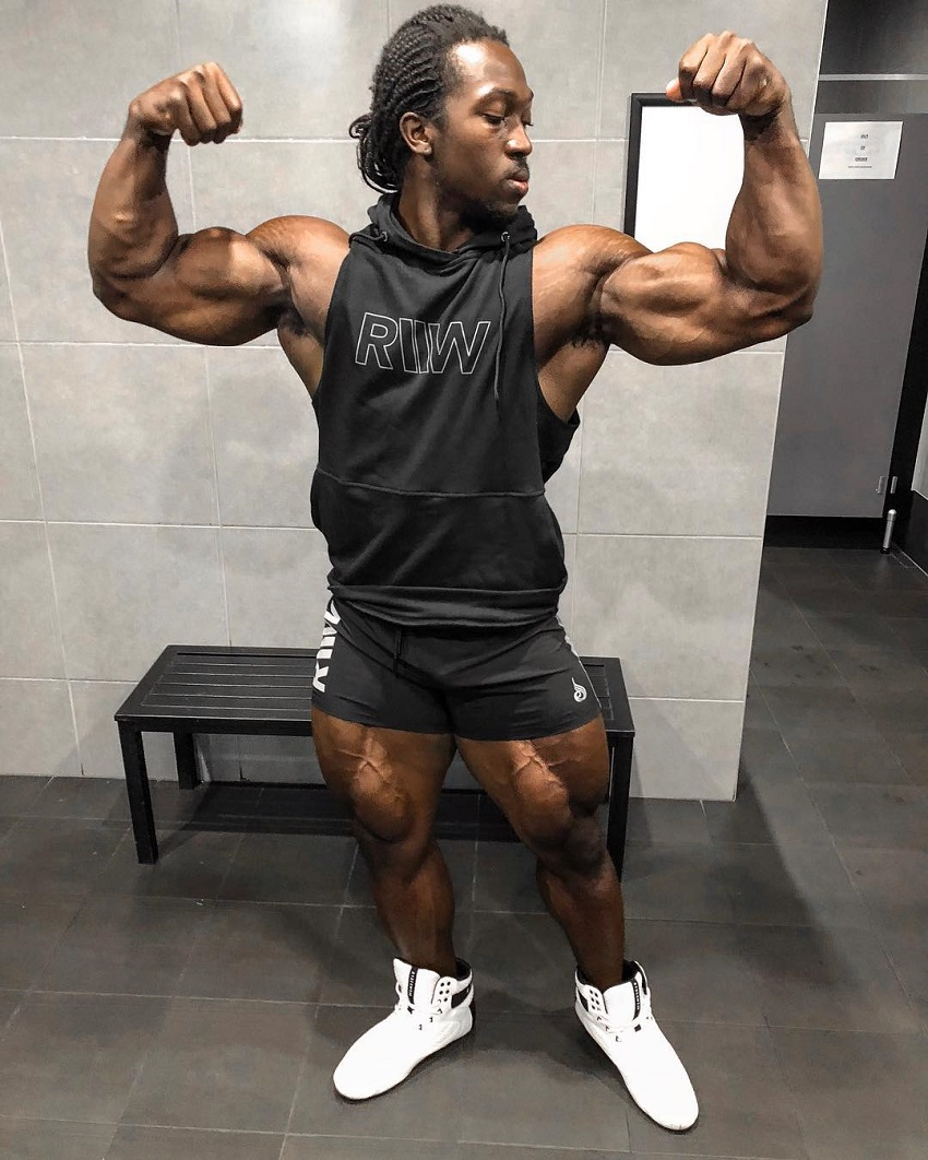 Kwame Duah flexing front double biceps in a black tank top