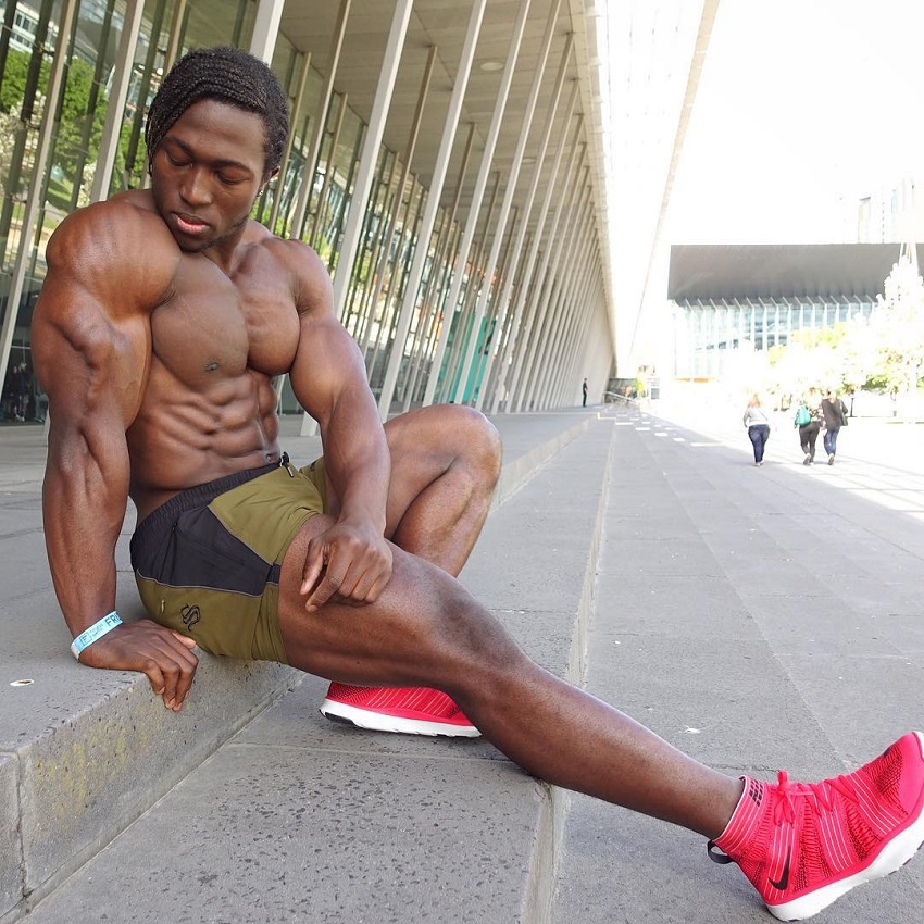 Kwame Duah flexing his triceps shirtless, looking ripped