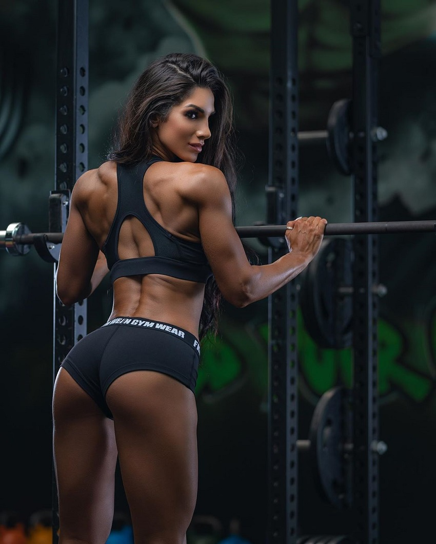 Libby Powell posing next to a smith machine looking curvy and fit