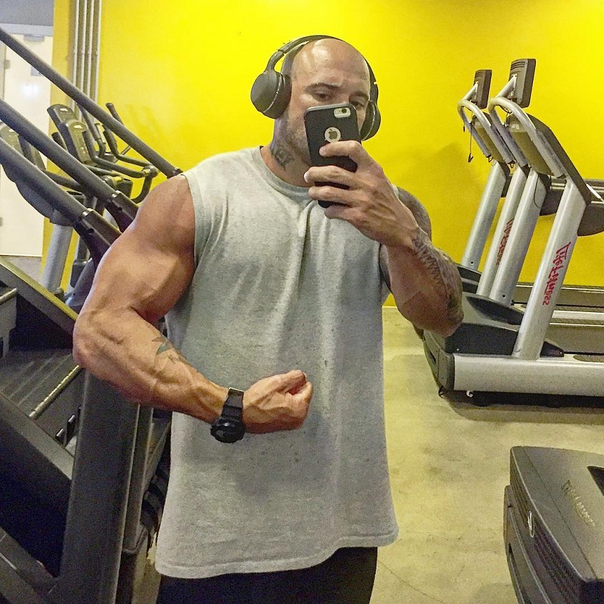 Marcello Rafaelli taking a selfie of his vascular and ripped arms in the cardio room