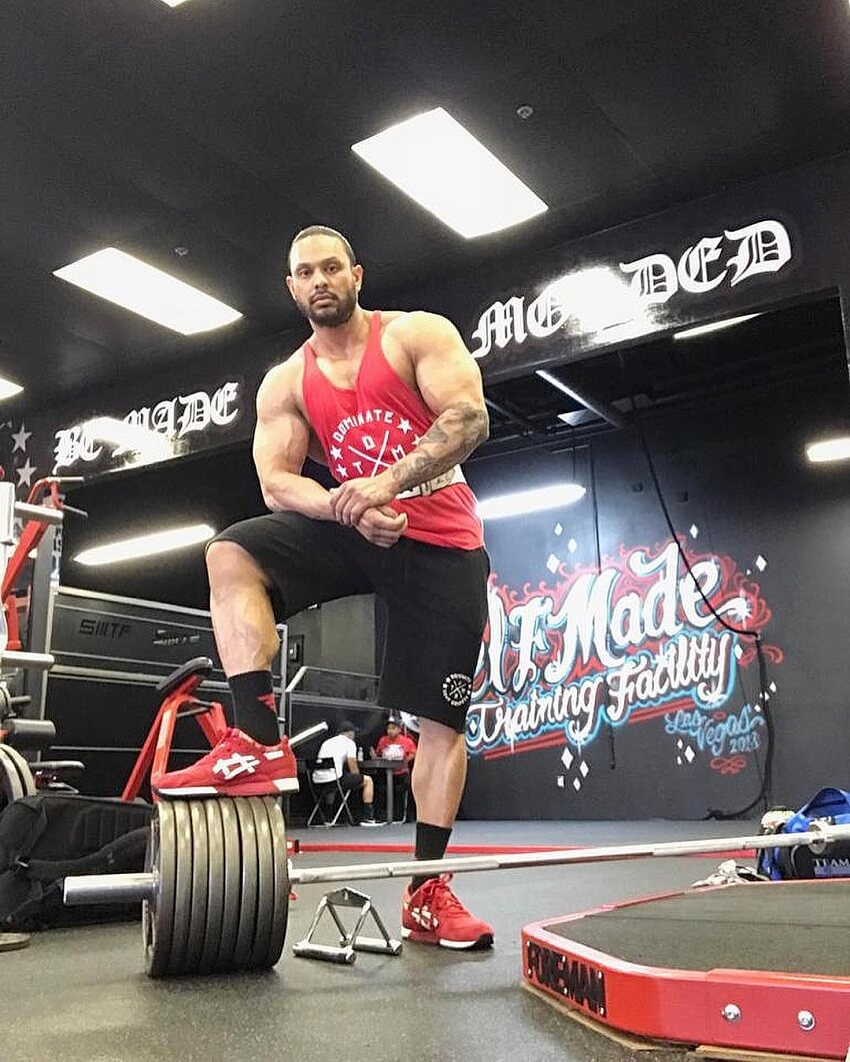 Mark Anthony posing in the gym next to a loaded barbell