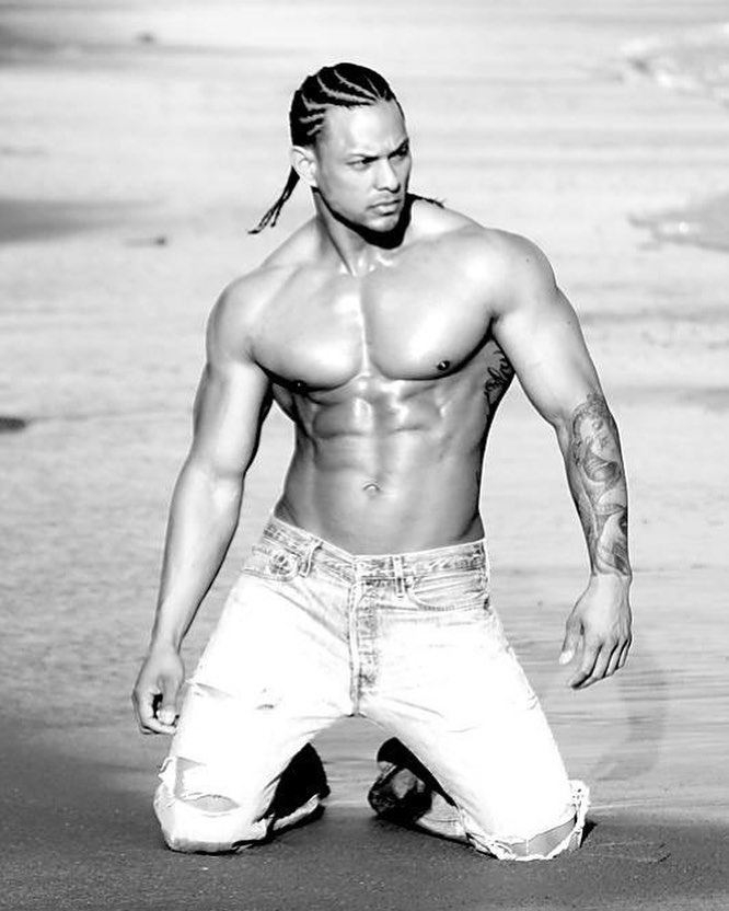 Mark Anthony posing on the beach in a fitness modeling event