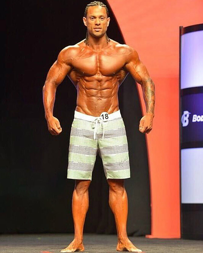 Mark Anthony posing shirtless on the Men's Physique stage