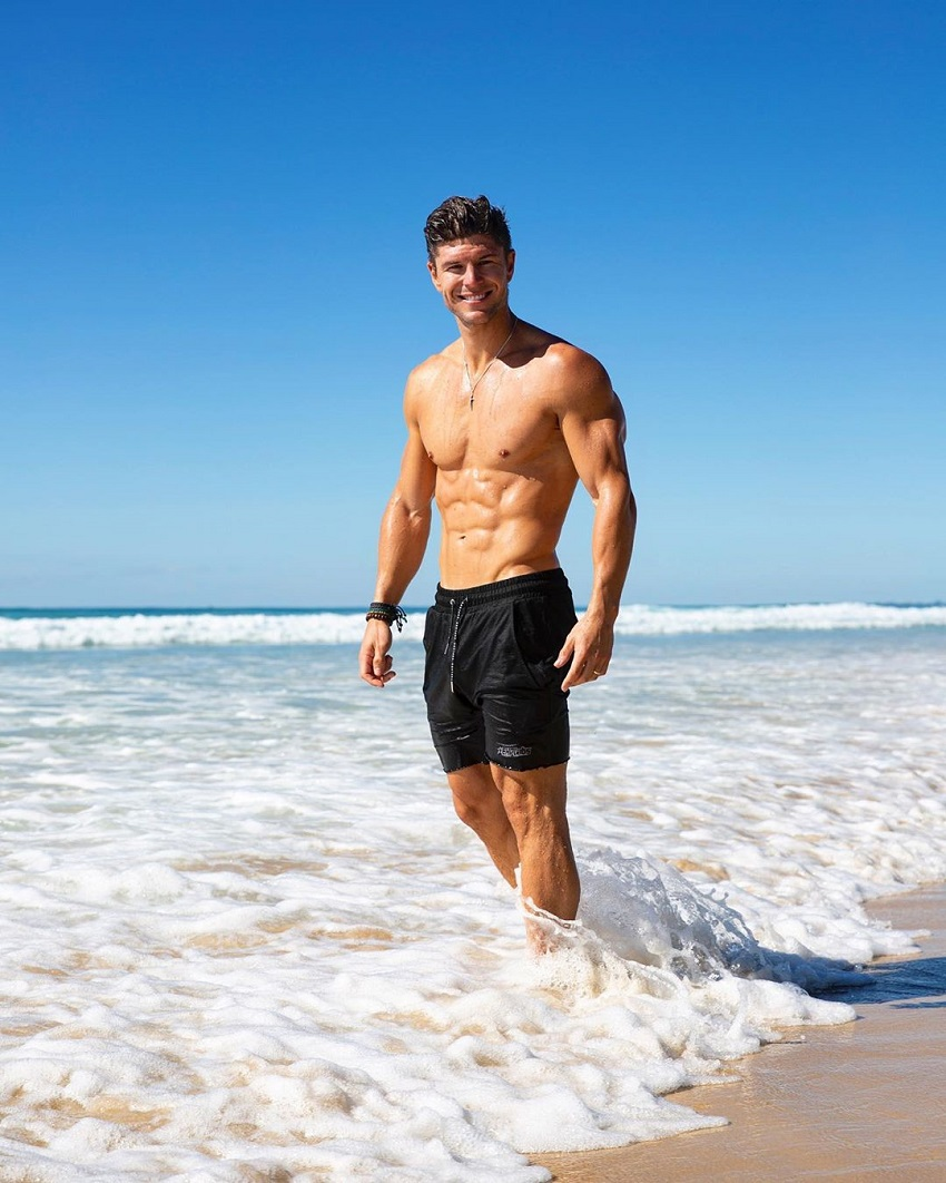 Mark Robinson standing shirtless on the beach and smiling, looking muscular