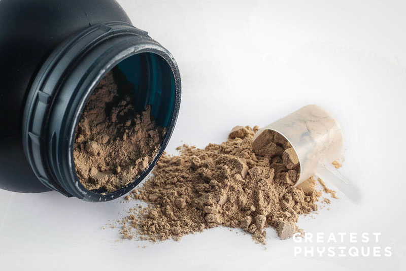 Tub of protein powder tipped onto its side with contents spilling out