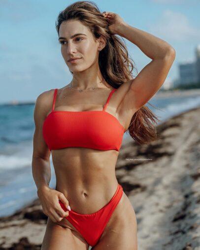 Andrea Thomas posing in a red bikini on the beach