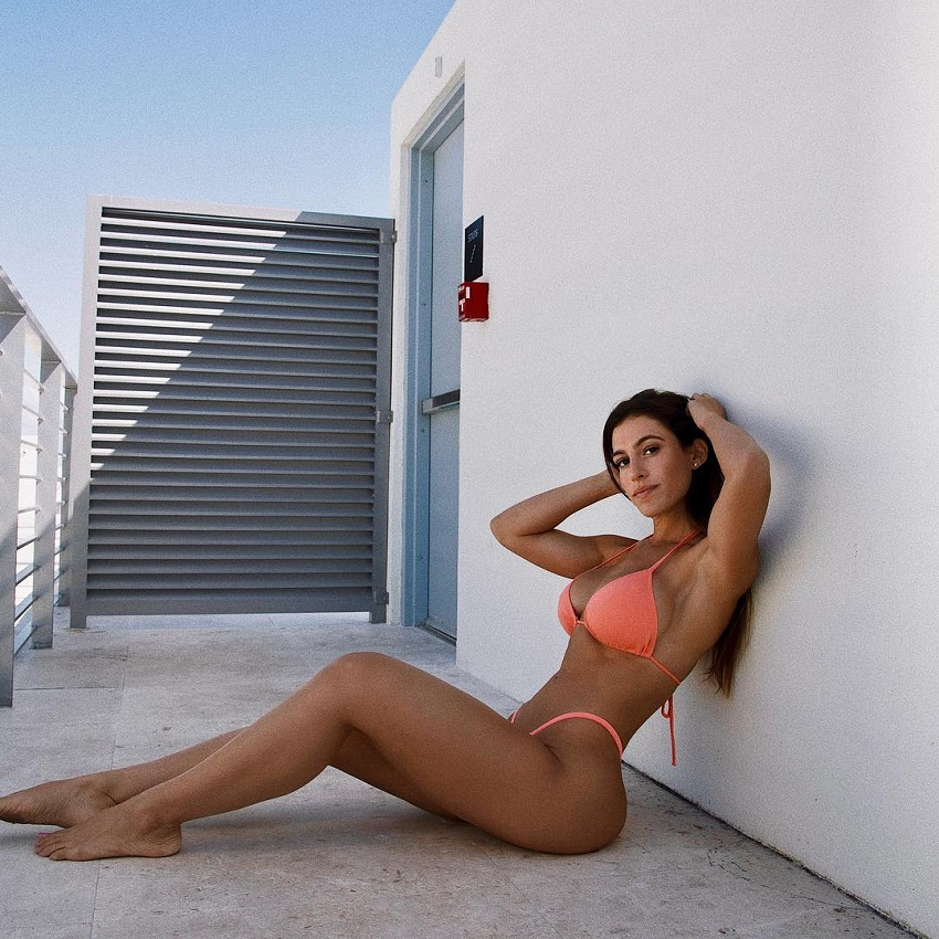 Andrea Thomas sitting on a rooftop in an orange bikini, looking fit and lean
