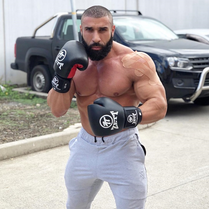 Basem Altakrity posing shirtless with boxing gloves