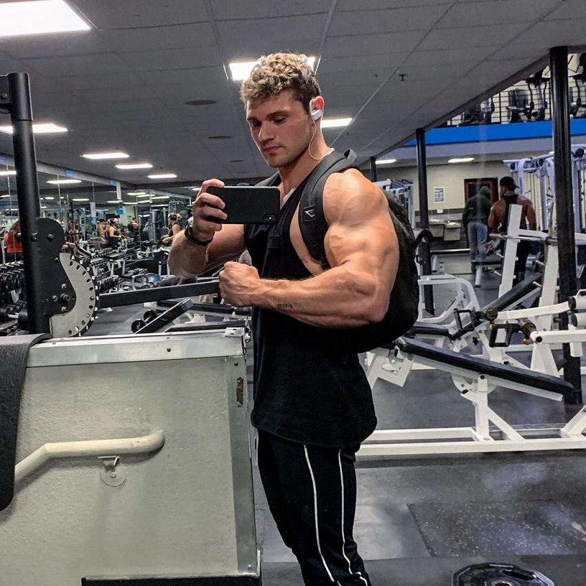 Chris Clark flexing his arms in the gym mirror