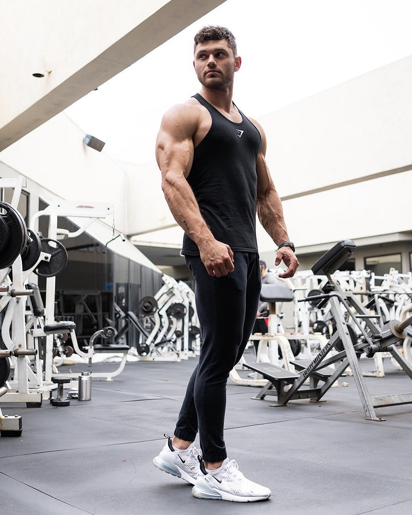 Chris Clark posing in the gym showing off his muscular arms