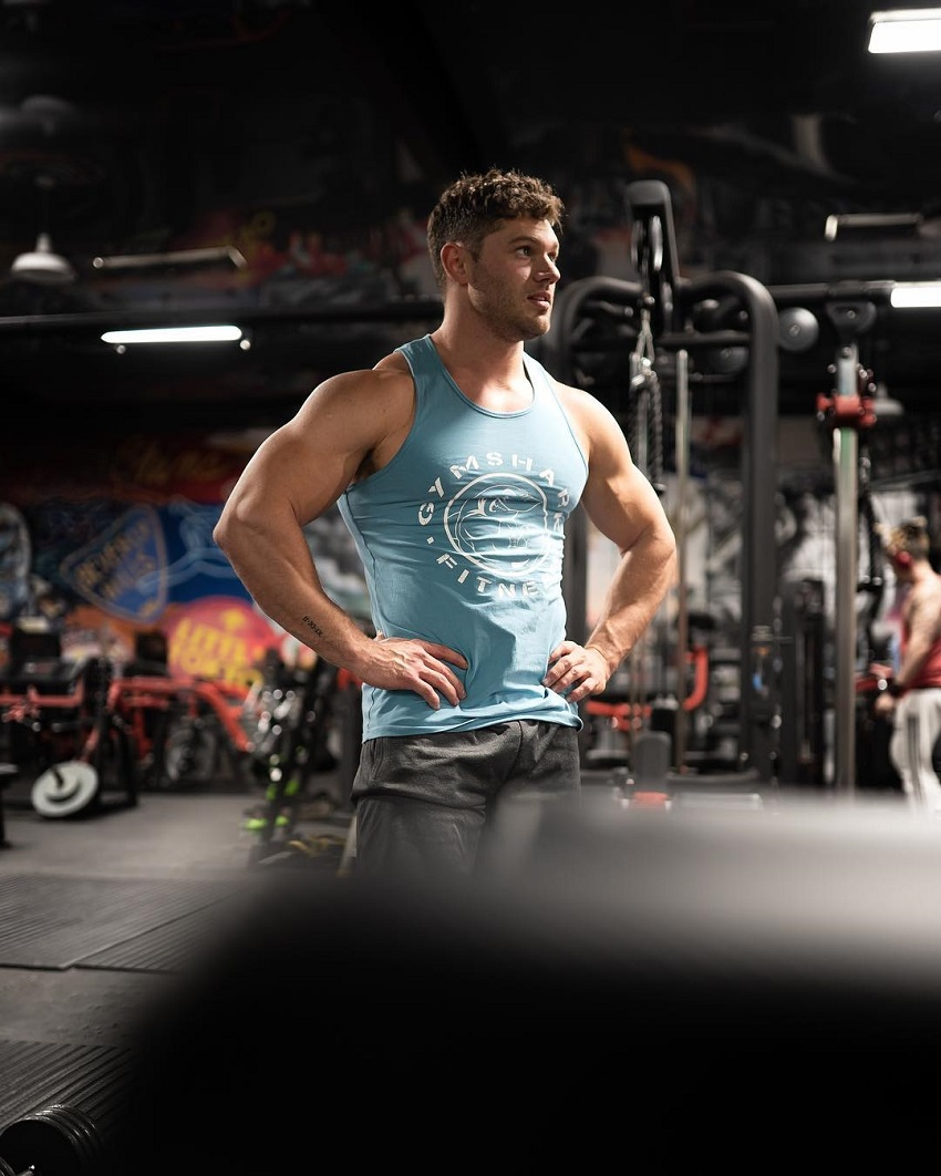 Chris Clark posing in a tank top in a gym