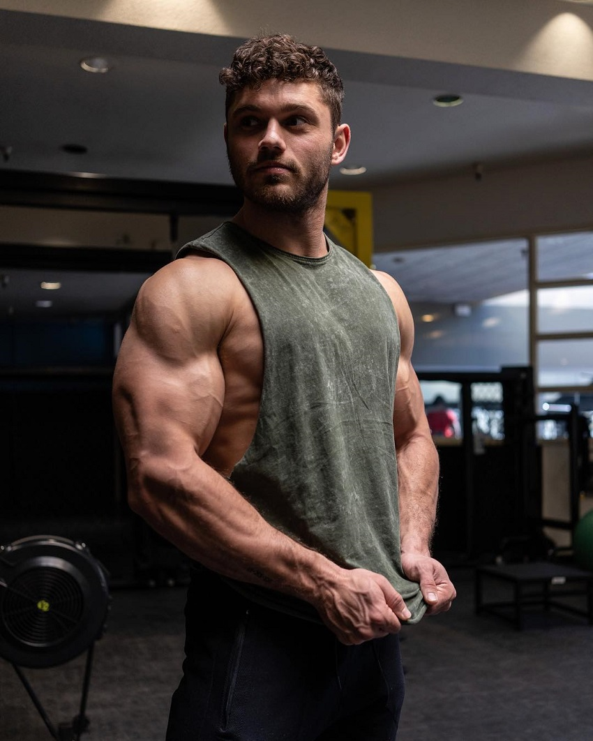 Chris Clark flexing his ripped triceps in a grey tank top