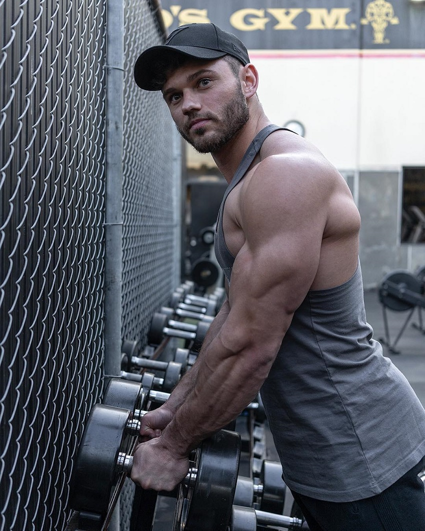 Chris Clark holding dumbbells looking muscular