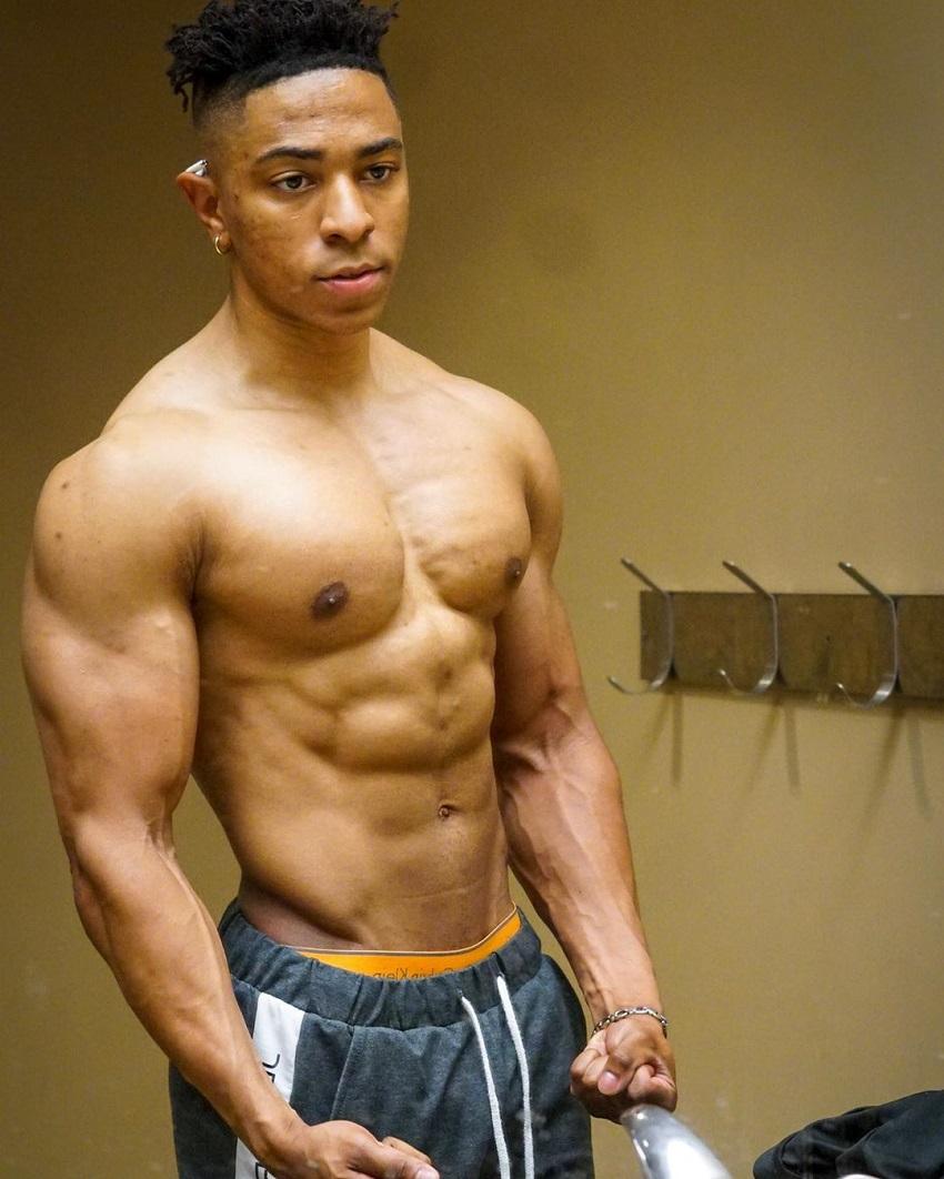 Evan Johnson posing shirtless in the gym locker room