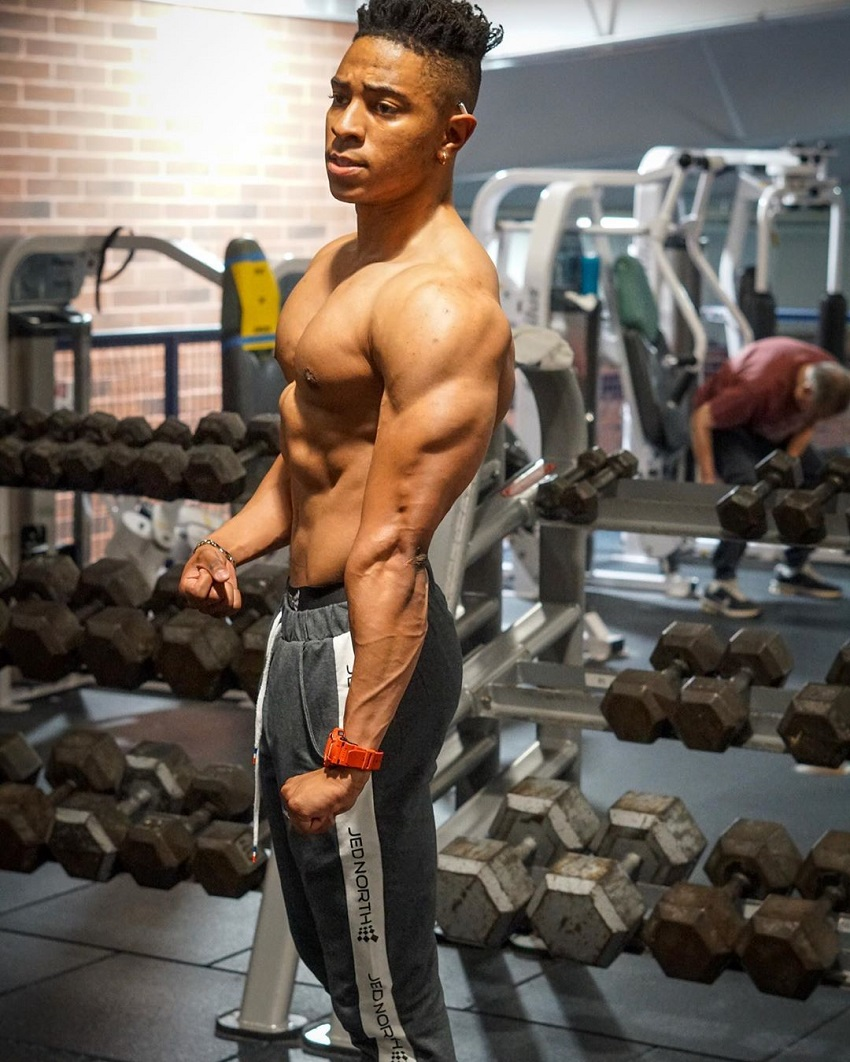 Evan Johnson flexing triceps shirtless in the gym