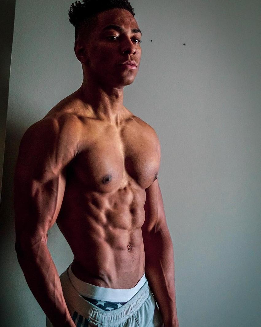 Evan Johnson posing shirtless looking ripped